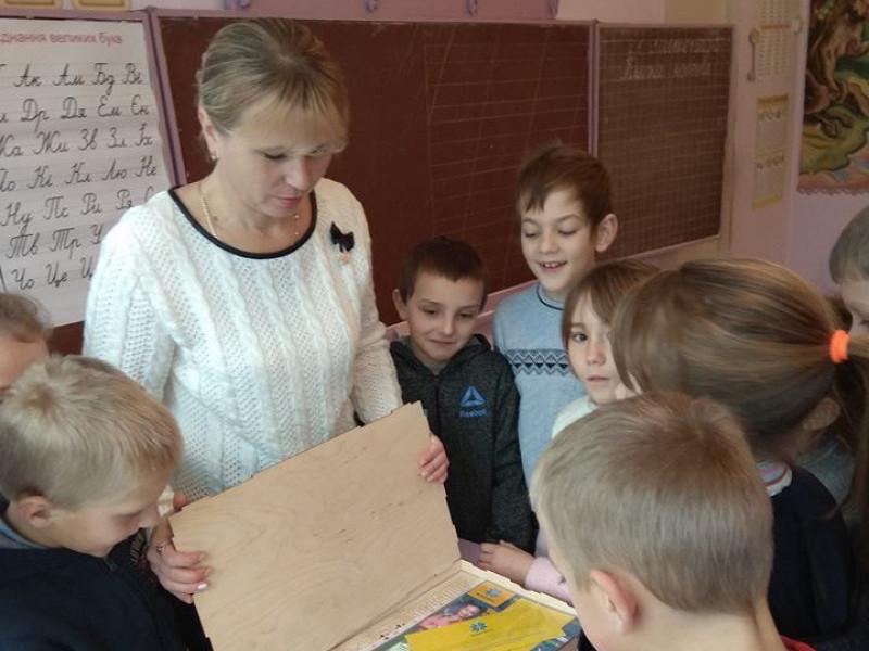Діти разом із вчителькою розпаковують приз